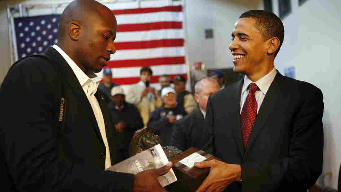 Barack Obama hands a gift from a supporter to his assistant Reggie Love during his 2008 campaign for presidency.