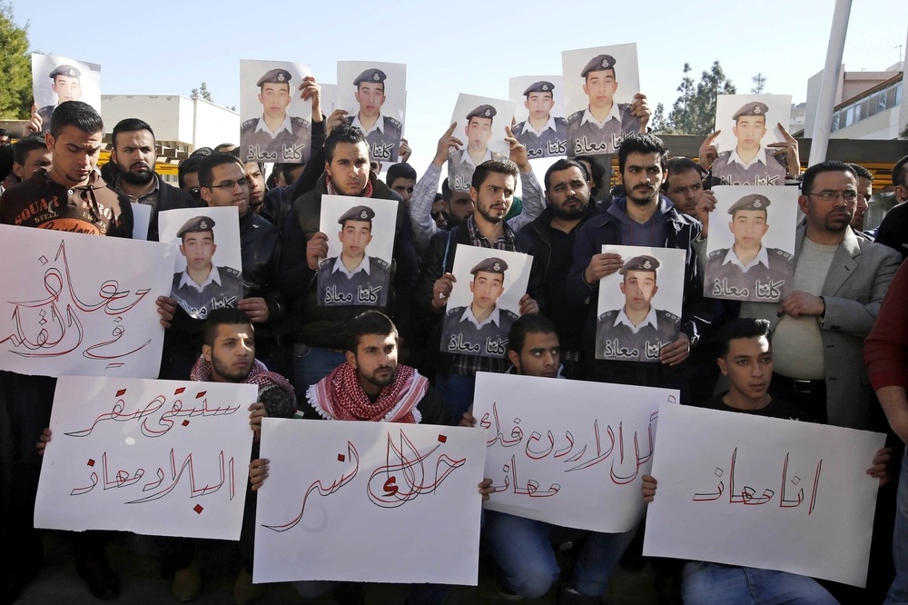 Supporters of Jordanian pilot  hold posters of him that read