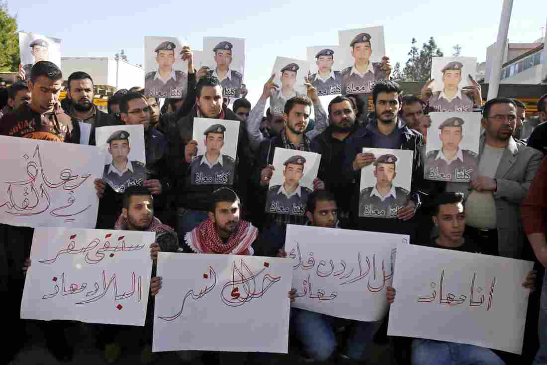 """Supporters of Jordanian pilot Lt. Muath al-Kaseasbeh hold posters of him that read, """"We are all Muath,"""" during a protest in Amman, Jordan, on Tuesday."""