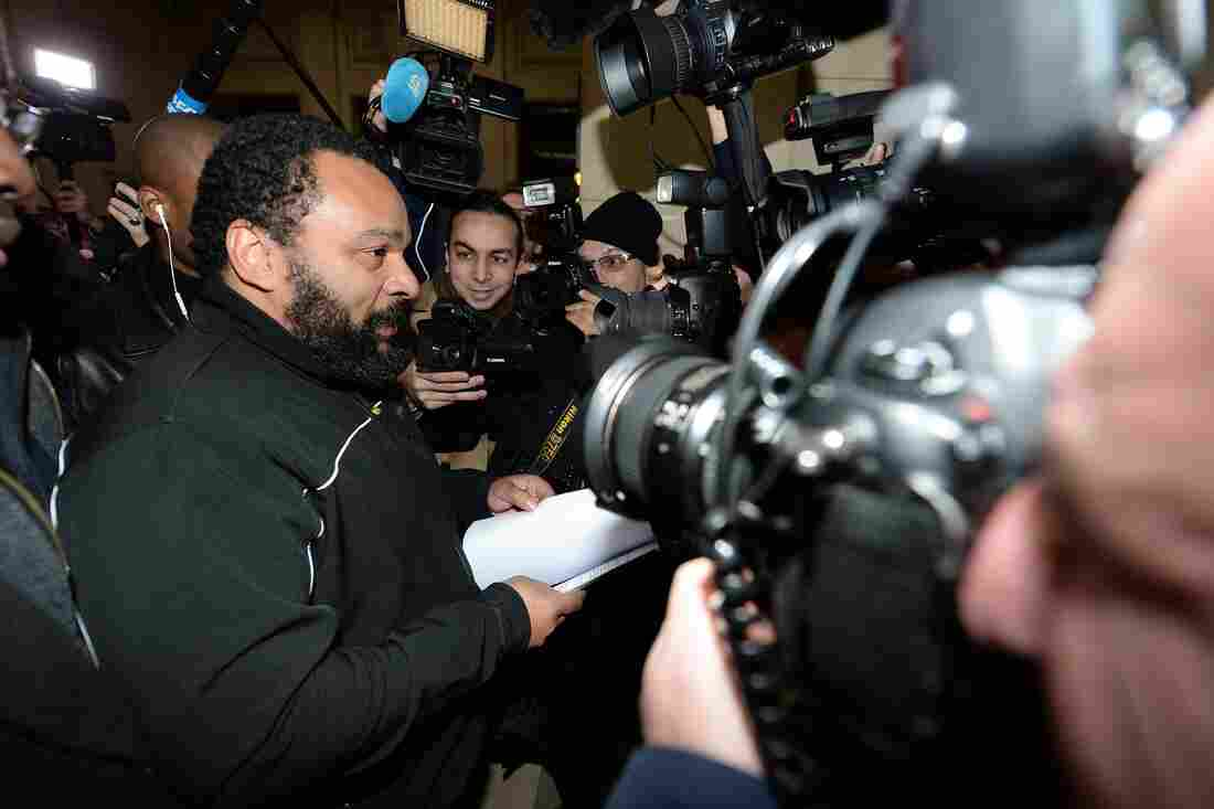 """French comedian Dieudonne M'Bala M'Bala arrives for his trial at the courthouse in Paris on Jan. 28. He goes on trial again today on charges of """"defending terrorism,"""" following remarks he made on Facebook after the deadly attack on the satirical weekly Charlie Hebdo."""