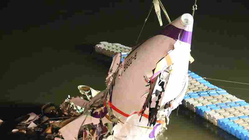 The mangled fuselage of a TransAsia Airways commercial plane is dragged to the river bank after it crashed in Taipei, Taiwan, on Wednesday.