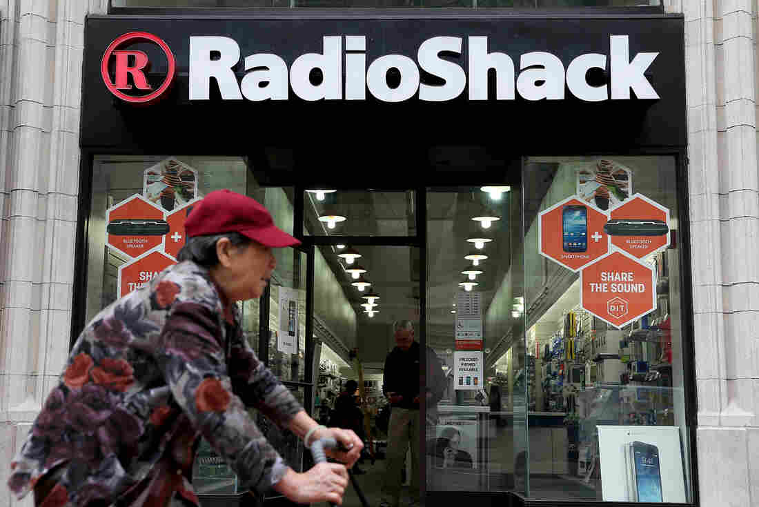 A person rides by a RadioShack store in San Francisco.