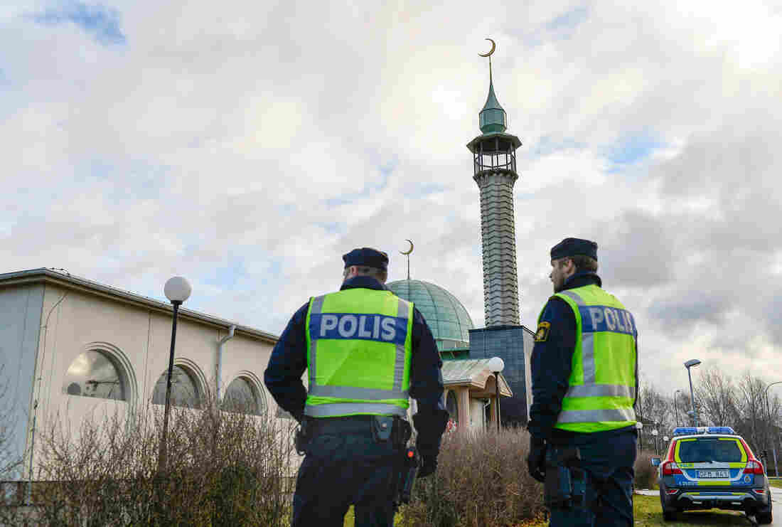 Two policemen stand outside a mosque in Uppsala, Sweden, last month. The mosque was firebombed on Jan. 1 in one of three arson attacks targeting the Muslim community in Sweden since Christmas Day.