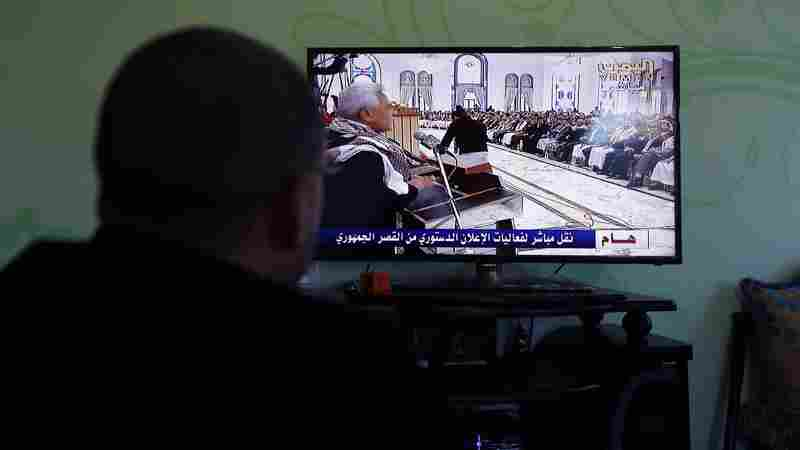 A Yemeni man watches a gathering on television organized by the Houthis announcing their vision for Yemen's government  in Sanaa, Yemen, on Friday.