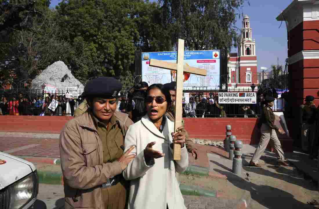 A policewoman detains one of the Indian Christians protesting against recent attacks on churches in the Indian capital outside the Sacred Heart Church in New Delhi, India, on Thursday.
