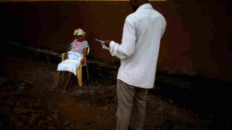 Survey teams are part of the Ebola army: They determine who's sick and send out burial teams when needed. Here, Osman Sow talks with Kadiatu, who is eight months pregnant and suspected of having the virus, as she waits at a health center in Freetown, Sierra Leone.