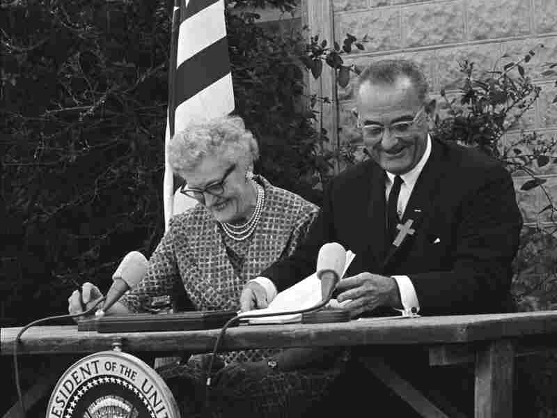 President Lyndon B. Johnson signs the ESEA in 1965 with Kate Deadrich Loney, the President's first schoolteacher.