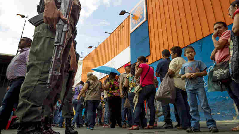 Shoppers queue outside the supermarket 'Dia a Dia' in Caracas, Venezuela, on Tuesday. The government took over stores of supermarket chain after alleging that it was hoarding food. According to many economists, government controls are making the economic crisis worse.