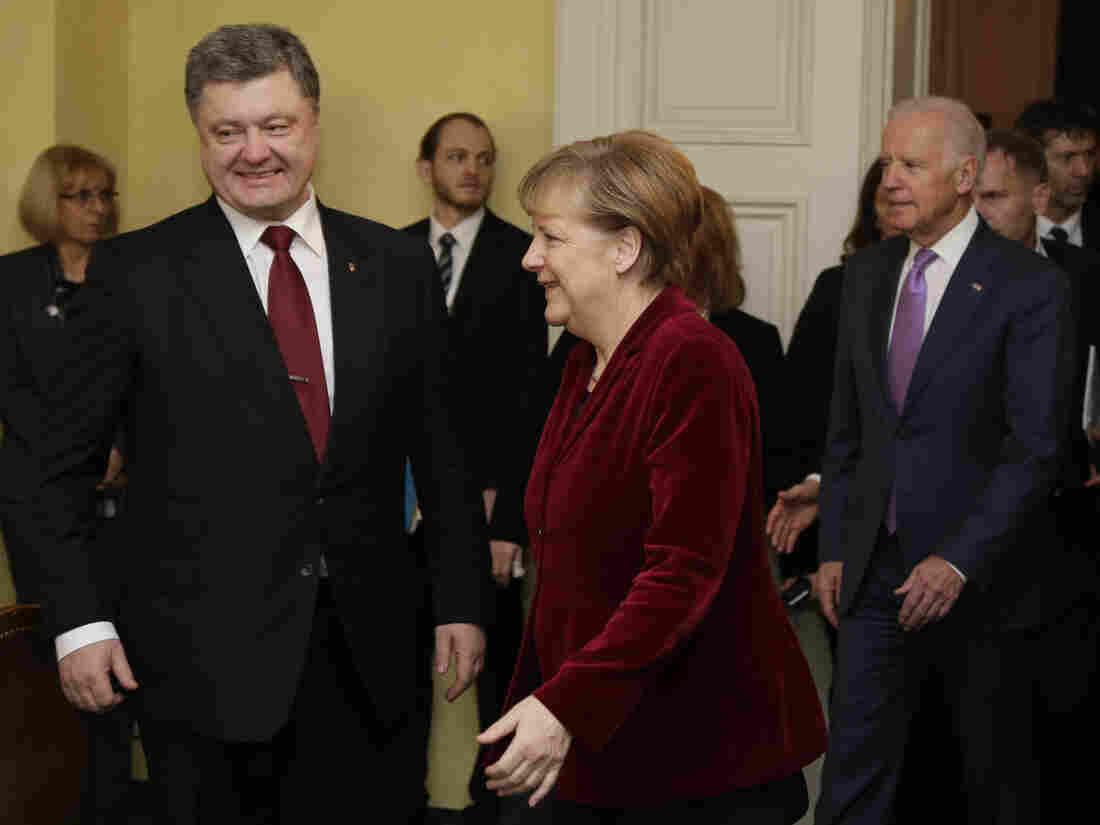 Ukrainian President Petro Poroshenko, left, German Chancellor Angela Merkel and U.S. Vice President Joe Biden, background right, arrive for a meeting in Munich, Germany on Saturday.