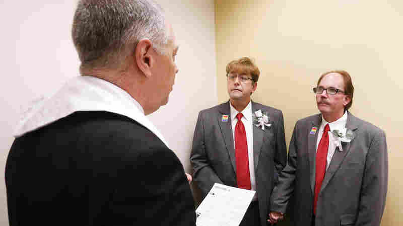 The Rev. Charles Perry of Unity Church, in Birmingham, Ala., marries Curtis Stephens, center, and his partner of 30 years, Pat Helms, Monday at the Jefferson County Courthouse. Alabama began issuing marriage licenses to same-sex couples Monday after the U.S. Supreme Court refused to block the marriages in the state.