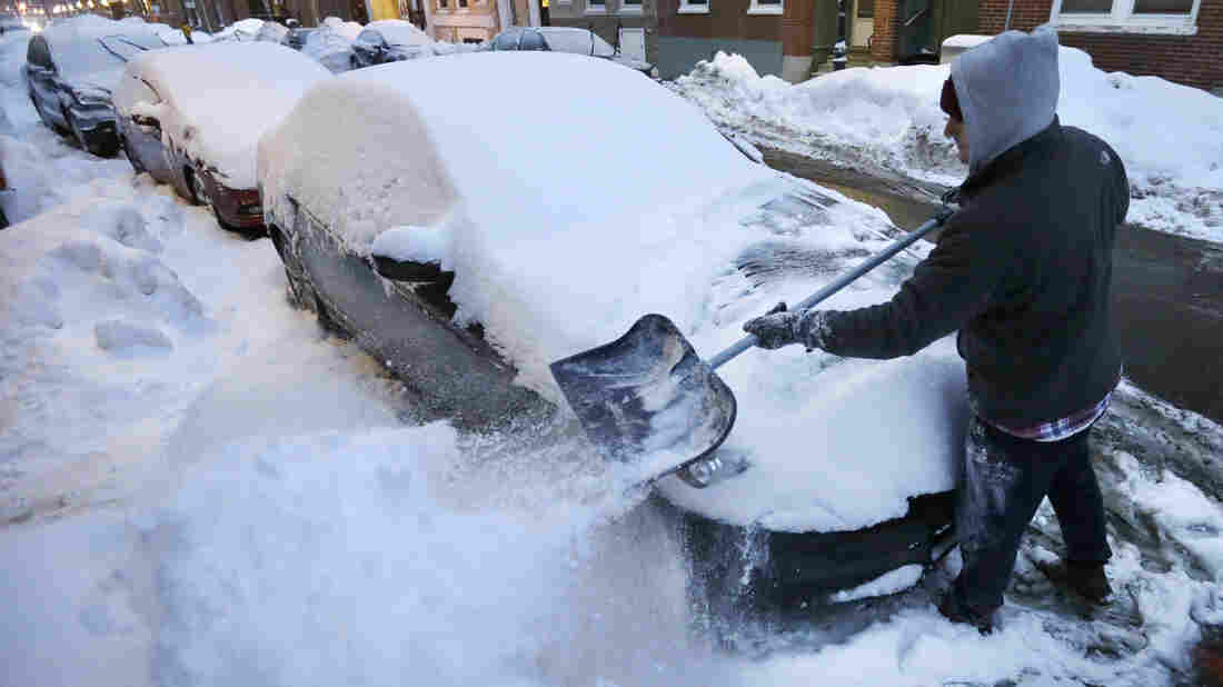 A man shovels snow from his car in Boston on Sunday, when a snowstorm began that isn't expected to finish until early Tuesday.
