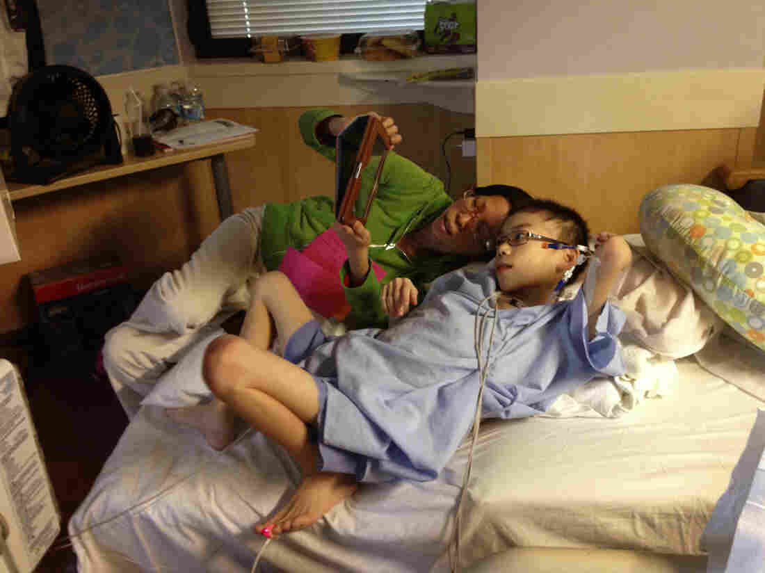Kathy Liu and her son Joey Xu talk to friends back home in Gainesville, Fla., from his hospital room in Cincinnati.
