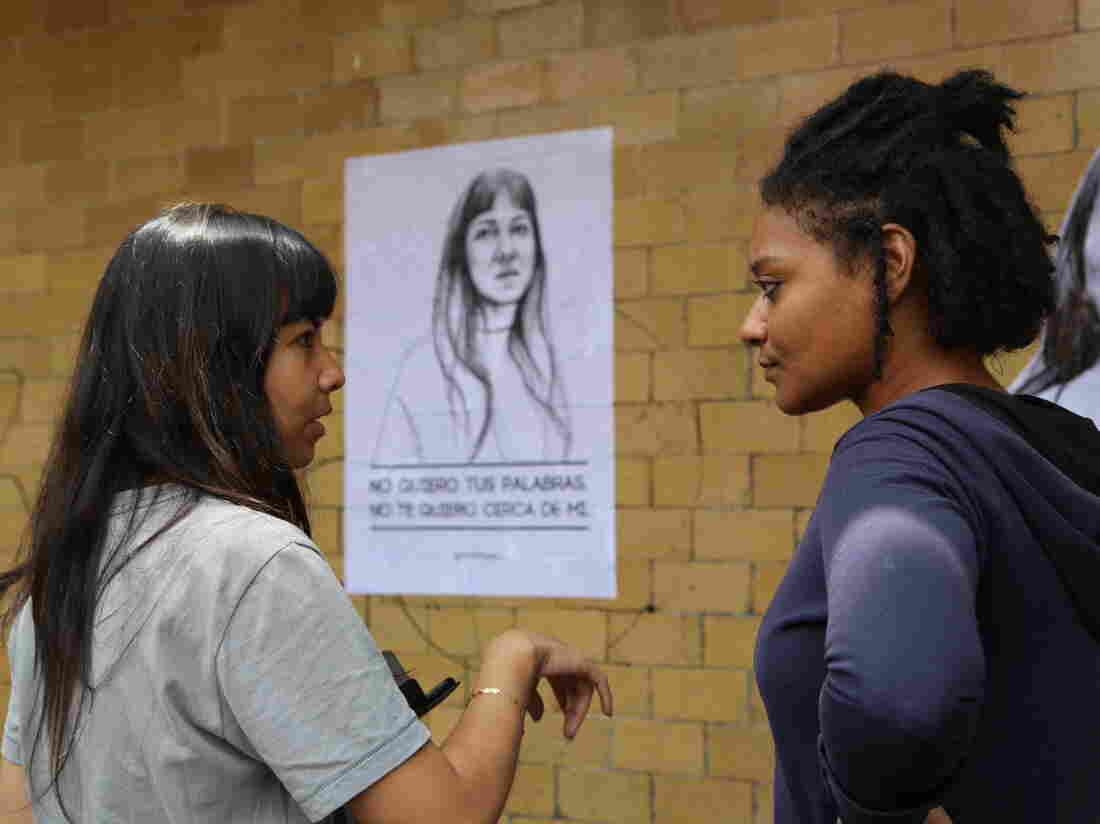 Artist Tatyana Fazlalizadeh, 29, talks to one of the women she depicted in poster she pasted on the streets of Mexico City.