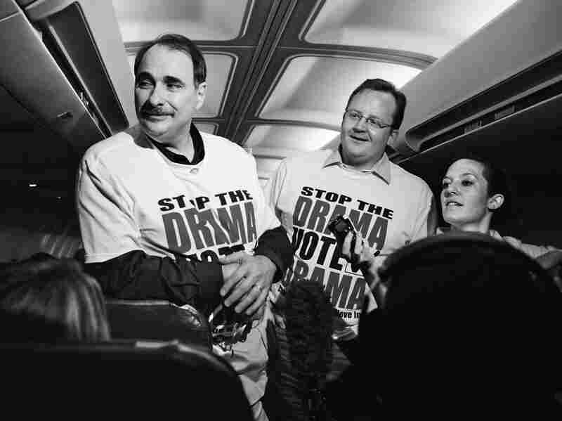 Chief campaign strategist David Axelrod (left) and communications director Robert Gibbs talk to members of the traveling press corps during a flight leading up to the Pennsylvania primary in 2008.