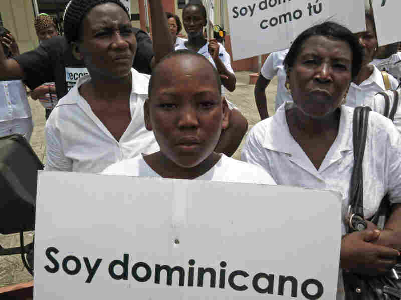 """Demonstrators from a 2013 protest against the Dominican Republic's constitutional amendment restricting citizenship hold signs saying """"I am Dominican just like you."""""""