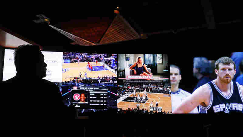 A man watches sports broadcast on screens at a sports book owned and operated by CG Technology in Las Vegas. CG Technology is asking the Nevada Gaming Control Board to allow betting on the Olympics.
