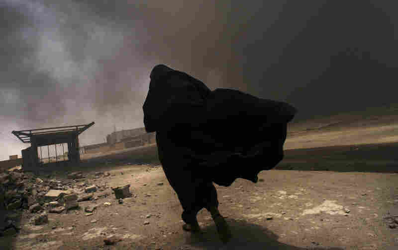 An Iraqi woman walks through a plume of smoke rising from a massive fire at a liquid gas factory as she searches for her husband in the vicinity in Basra, Iraq, May 2, 2003.