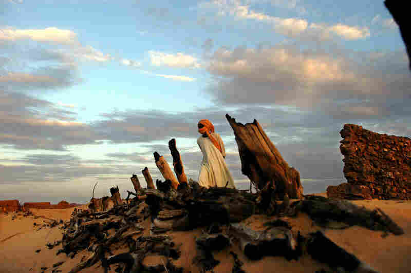 A Sudanese Liberation Army soldier walks through the remains of Hangala village, which was burned by Janjaweed near Farawiya, in August 2004. Thousands of ethnic Africans fled their villages in search of shelter in the mountains or in neighboring Chad because of continuing attacks on civilians.