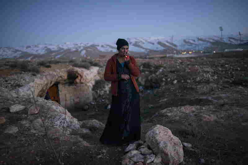Dalal, 21, a Syrian refugee from the Damascus suburbs stands in front of the cave she and her family have been staying in since crossing into Baalbak, Lebanon. Jan. 22, 2013.