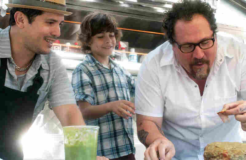 In Chef, Jon Favreau (right) plays a chef who leaves his post at a respected LA restaurant to launch a food truck with his son (Emjay Anthony, center) and a former line cook (John Leguizamo).