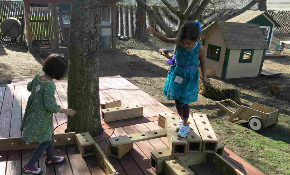 One child's stage is another student's obstacle course. Preschoolers at Bing Nursery School play with outdoor blocks.