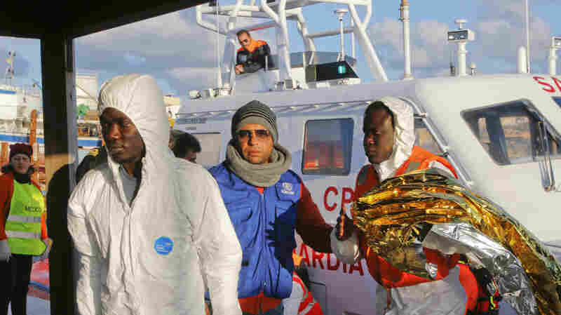 Migrants who survived a shipwreck are escorted as they arrive at the Lampedusa harbor on Wednesday. Some 300 others drowned in the latest such disaster triggered by people fleeing conflicts in North Africa.