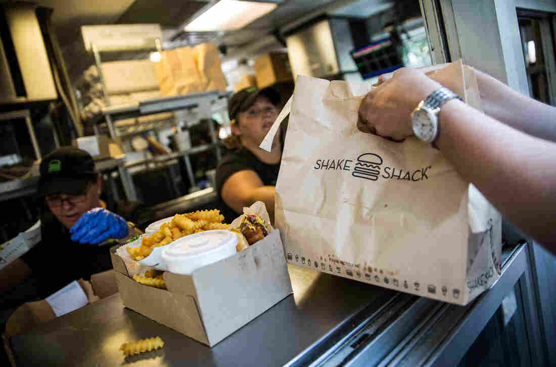 Customers pick up their orders from a Shake Shack in New York City. It's one of the restaurants whose labor practices are detailed in the ROC United Diners' Guide app.