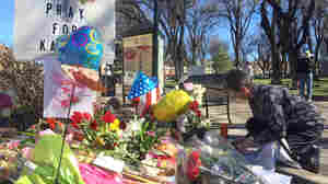 A woman kneels near a makeshift memorial for Kayla Mueller in Prescott, Ariz.