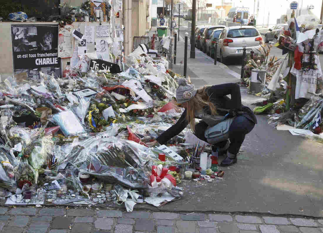 A woman looks at flowers placed near the headquarters of the magazine Charlie Hebdo in Paris, on Feb. 7. Islamist extremists stormed the offices of the satirical newspaper,  killing 12 people in January.