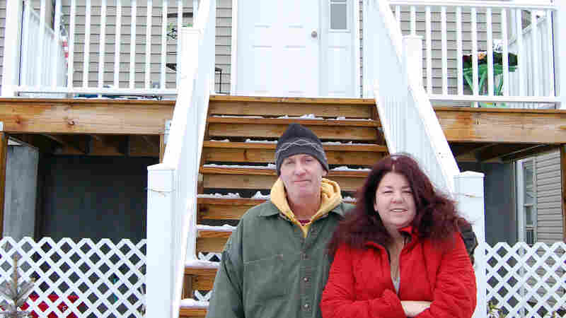 Dan and Eileen Stapleton in front of their post-Sandy home in Long Beach, N.Y. They say it would cost taxpayers less if insurance just settled their claim.