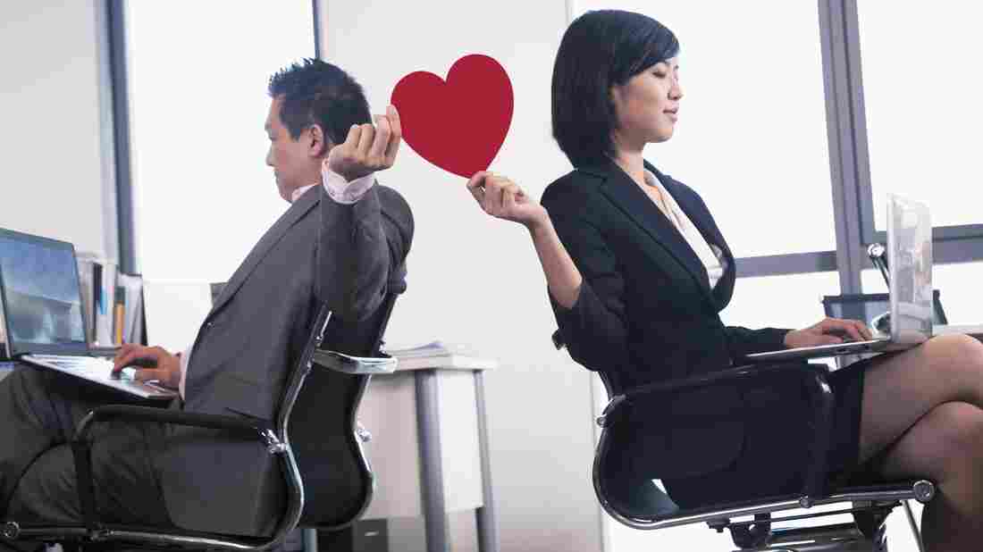Work romance between two business people holding a heart.