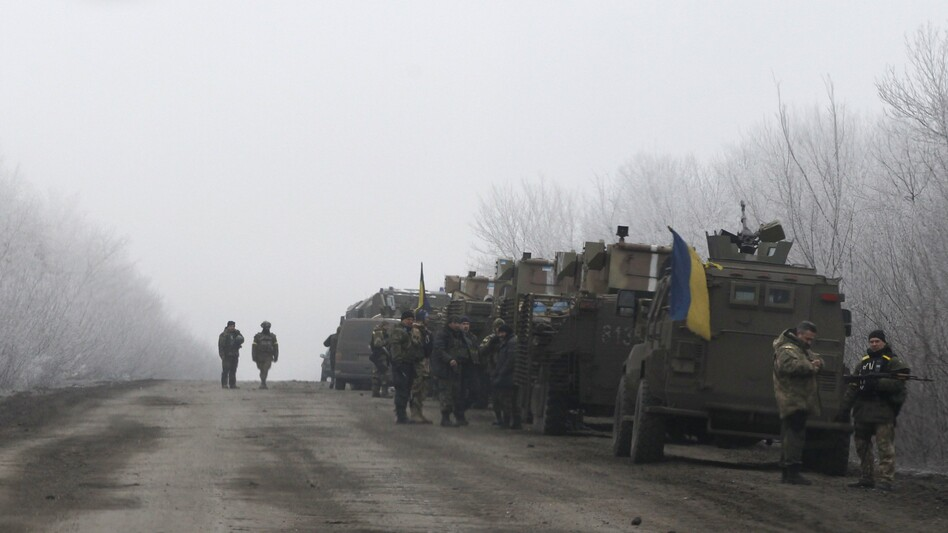 A Ukrainian military convoy stops on the road between the towns of Debaltseve and Artemivsk, Ukraine, on Saturday, hours before a cease-fire agreement is set to go into effect. (Petr David Josek/AP)