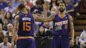 Phoenix Suns forward Marcus Morris, left, congratulates his twin brother, Markieff, after he scored against the Sacramento Kings during the fourth quarter of a game on April 16, 2014.