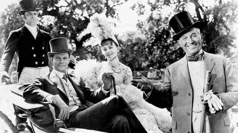 This scene from the 1958 film Gigi shows stars Louis Jourdan sitting across from Leslie Caron, with Maurice Chevalier standing to the front of them.
