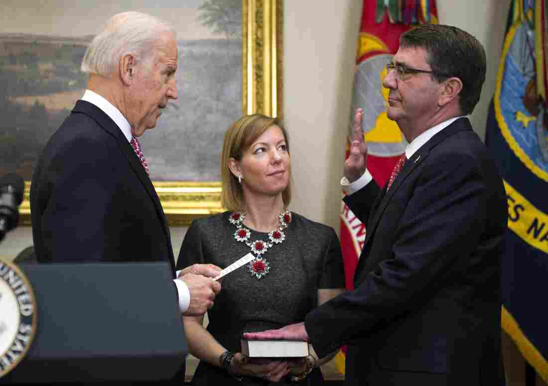 Vice President Biden swears in Ashton Carter, as the new Secretary of Defense's wife, Stephanie, holds the Bible for a ceremony in the White House Tuesday.