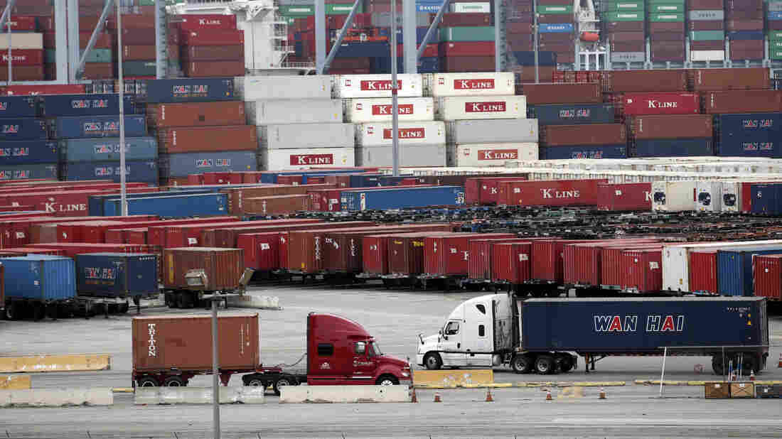 Trucks move containers at the Port of Long Beach in California on Tuesday. Contract negotiations between dockworkers and shipping companies have led to a slowdown on the piers.