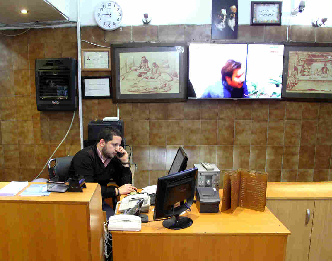 David Shumer handles takeout orders at a kosher restaurant in Tehran that his family has run for 35 years. He has a comfortable, middle-class life and says he is happy in Iran. An image of Ayatollah Ruhollah Khomeini and Ayatollah Ali Khamenei,  the past and present supreme leaders of Iran, hangs on the wall.