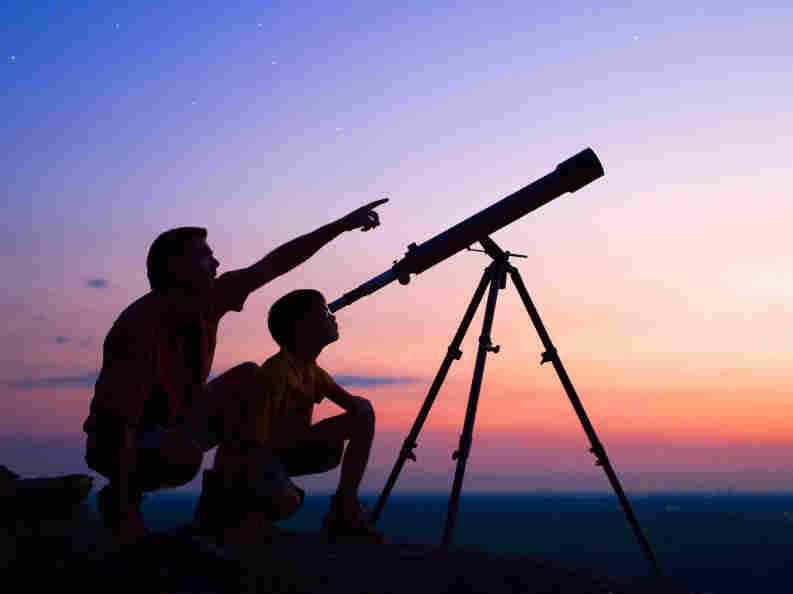 A boy and his dad look through a telescope.