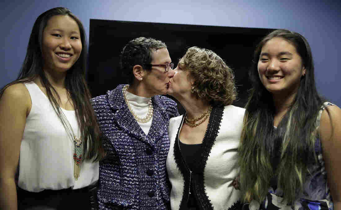 Sarah Goodfriend (left center) and Suzanne Bryant share a kiss Thursday as they pose with their daughters, Dawn Goodfriend (left) and Ting Goodfriend following a news conference in Austin.