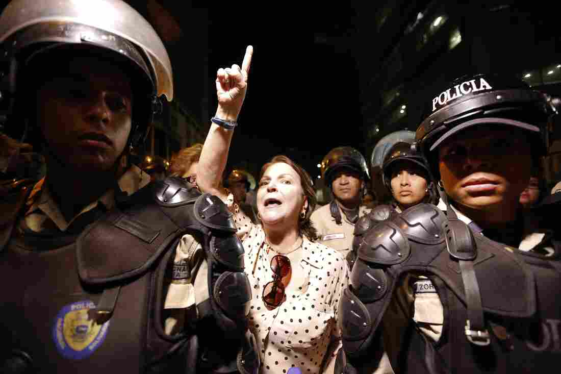 Mitzy Capriles de Ledezma, the wife of Caracas Mayor Antonio Ledezma, chants for the release of her husband, as she stands behind two national police officer on guard outside intelligence service police headquarters, in Caracas on Thursday.