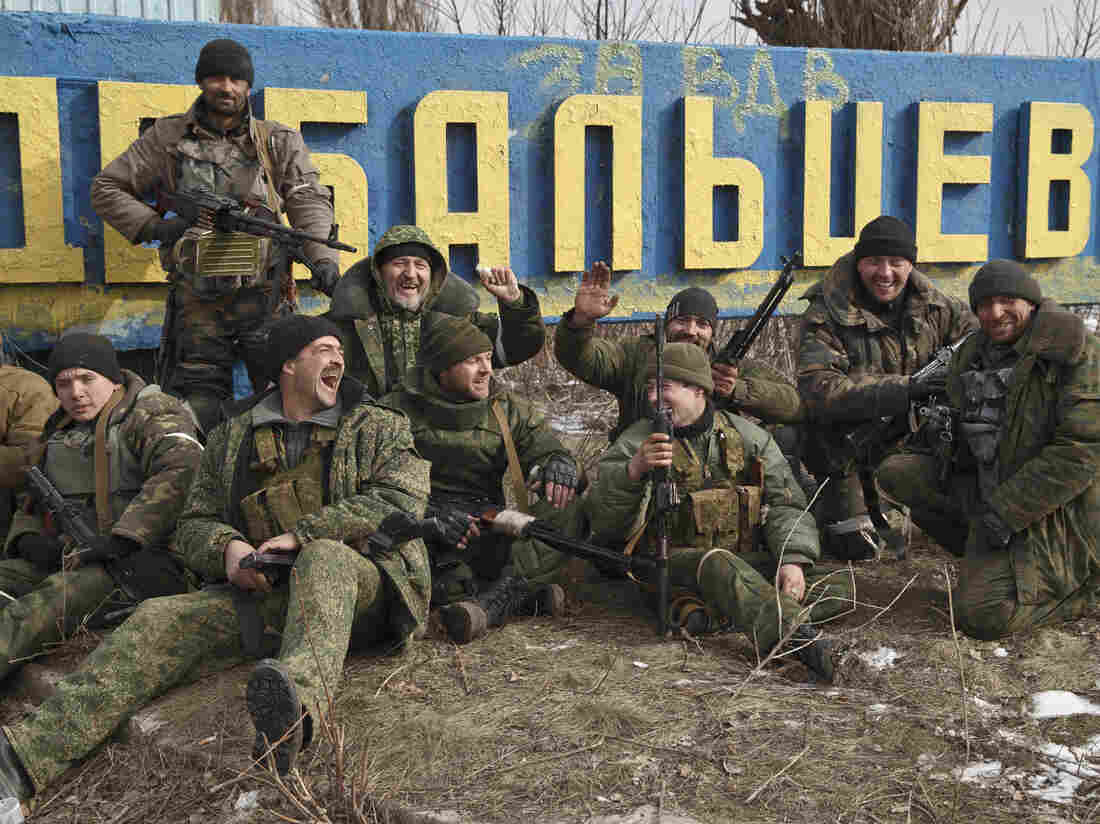 Russia-backed rebels pose by a road sign at the entrance in Debaltseve, Ukraine, on Friday after their post-cease-fire seizure of the strategic town.