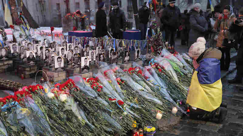 "People pay their respects Friday in honor of the ""Heavenly Hundred"" who were killed a year ago on Independence Square in Kiev, Ukraine."