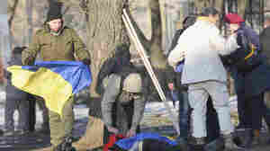 A man holds a Ukrainian flag as he cover the body of a victim of an explosion in Kharkiv, Ukraine, on Sunday.