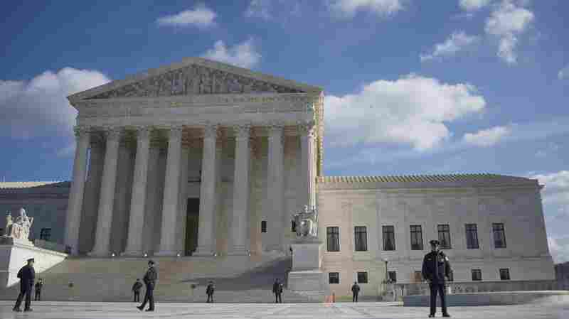 U.S. Supreme Court police stand on the plaza in front of the courthouse in January. The court heard arguments Monday about whether an American had a right to know why their foreign-national spouse had been refused entry into the country.