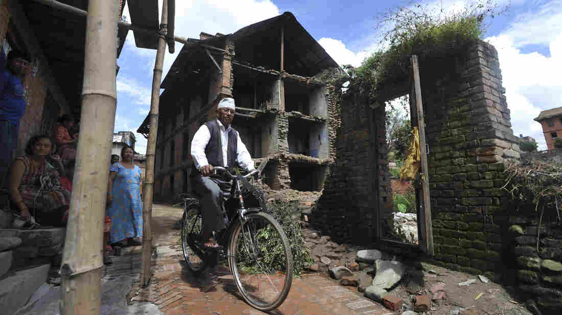 A bicyclist passes a home damaged in a 2011 earthquake at Bhaktapur, some 7 miles southeast of Kathmandu.