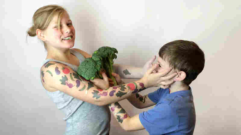 Siblings Jessica and Oliver Schaap of Holland, Mich., test out the temporary vegetable tattoos known as Tater Tats.