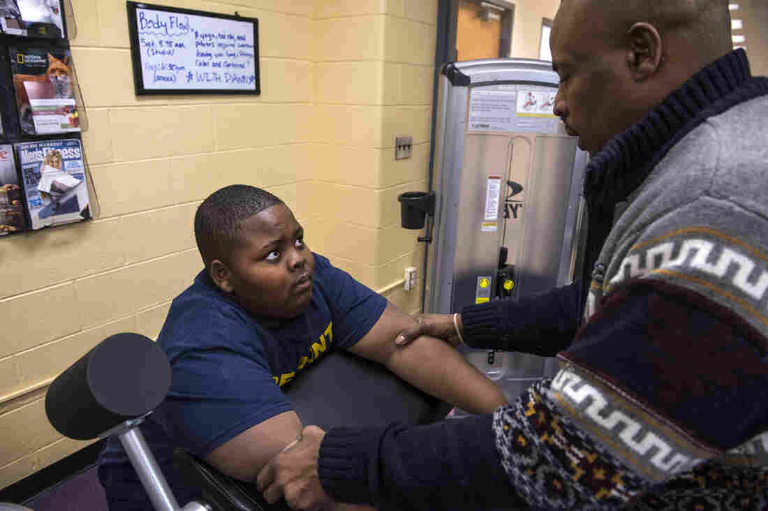 Silvester Fullard encourages his son during a workout at the Christian Street YMCA in Philadelphia. Tavestsiar once relied on food as a comfort to deal with his trauma, his dad says. But no more.