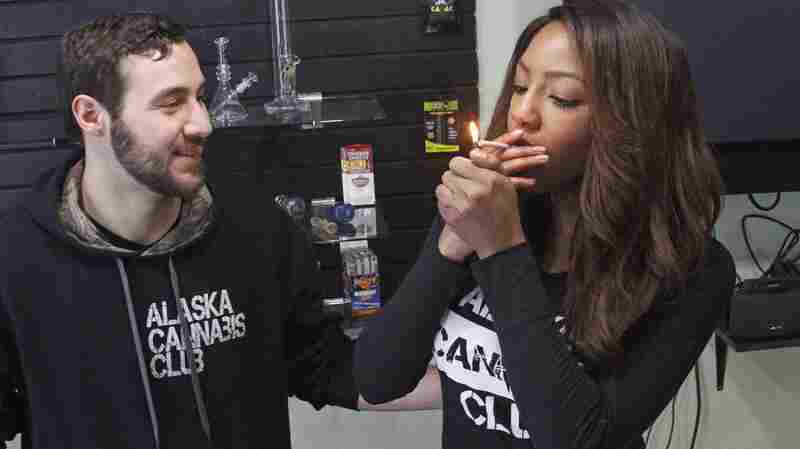 Leaders of the Alaska Cannabis Club share a joint at their medical marijuana dispensary in Anchorage. On Tuesday, Alaska became the third state in the nation to legalize recreational marijuana use.