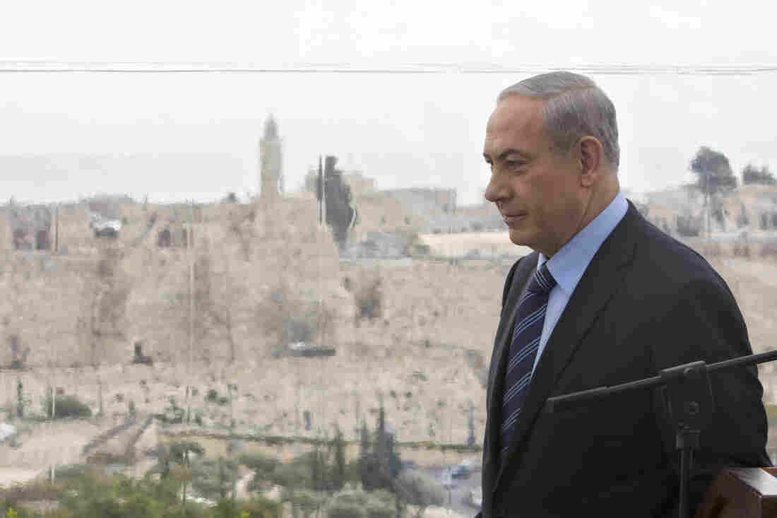 Israeli Prime Minister Benjamin Netanyahu  walks past a window overlooking the Old City of Jerusalem.