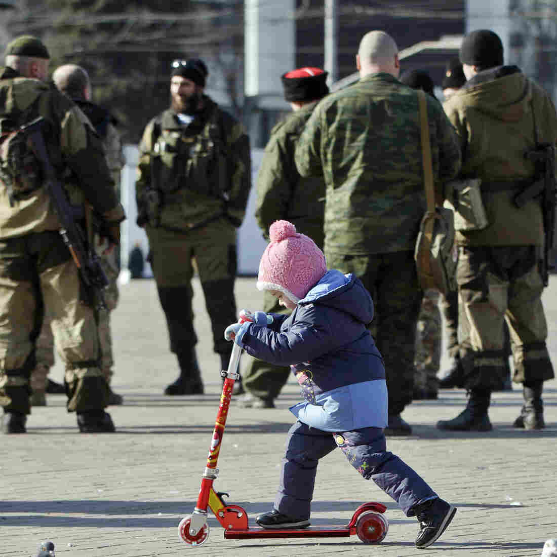 A child plays near Russia-backed separatists in Donetsk, Ukraine, Monday. Separatists say they've begun to withdraw heavy weapons from the front line — a claim that monitors say they can't verify.